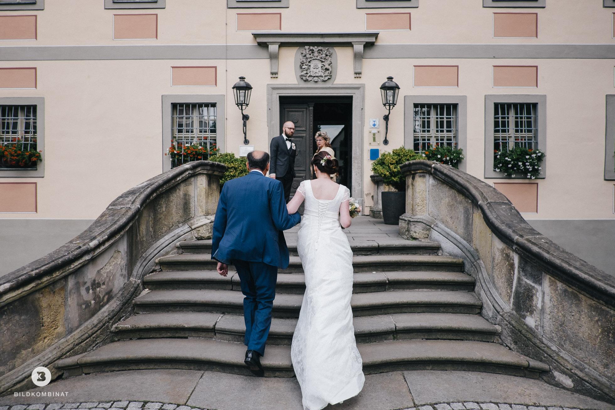 Braut und Vater schreiten zum Bräutigam